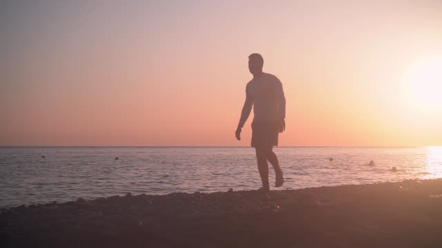 A young man walks along the shore against the backdrop of a sunset. A man walks along the beach on a sunset background.