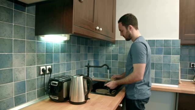 Joven lavar los platos en la cocina en casa - vídeo