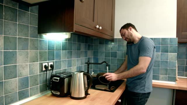 Hombre joven de lavar los platos mientras habla por teléfono móvil en la cocina - vídeo
