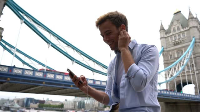 Young man watching a video and listening headphones while sitting near the London bridge