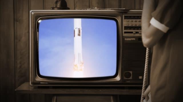 vídeos y material grabado en eventos de stock de 1969. joven relojante en casa el metraje histórico del apolo 11 de la nasa se lanza en un viejo televisor retro. tono sepia. - historia