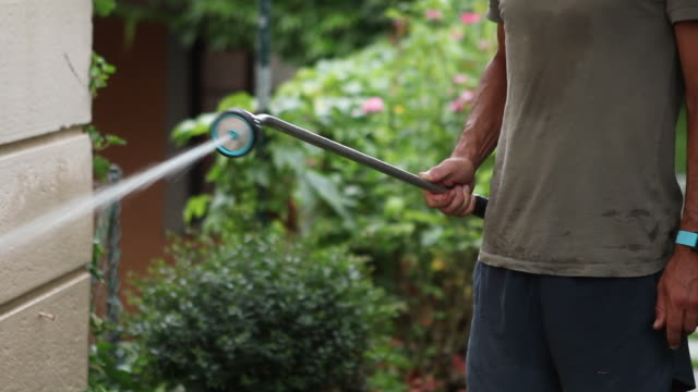 Young man watering garden. Person spraying water in backyard