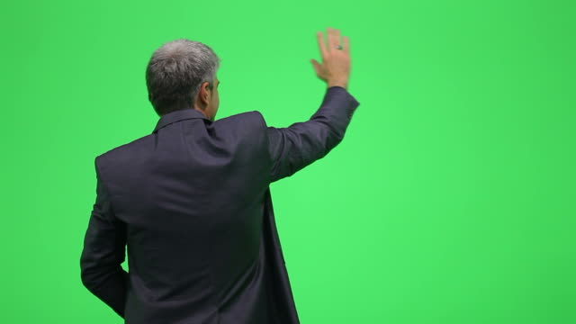 A young man waving, isolated on a green chroma key video