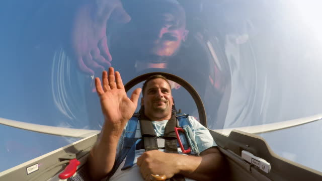 LD Young man waving while sitting in the back of the glider doing loops in the sunny sky