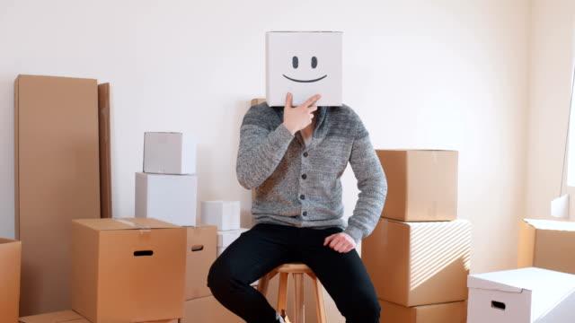 ung man bära uttryckssymbol låda på huvudet - flyttlådor bildbanksvideor och videomaterial från bakom kulisserna