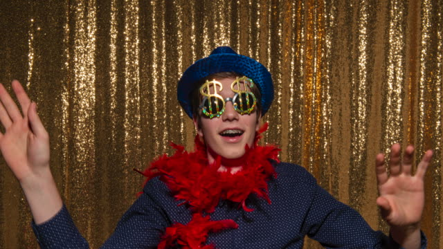 Young man wearing a blue glitter hat and scarf and having fun posing in the photo booth