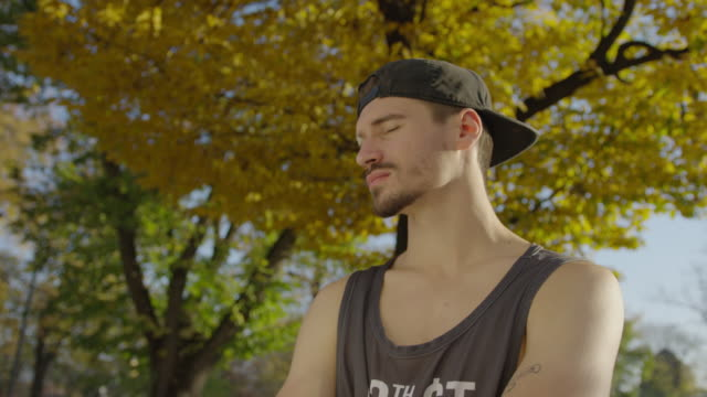 vídeos de stock, filmes e b-roll de homem novo que desgasta um tampão - boné