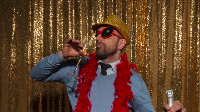 Young man wearing a glitter hat with red glasses and scarf taking fun photos in the photo booth