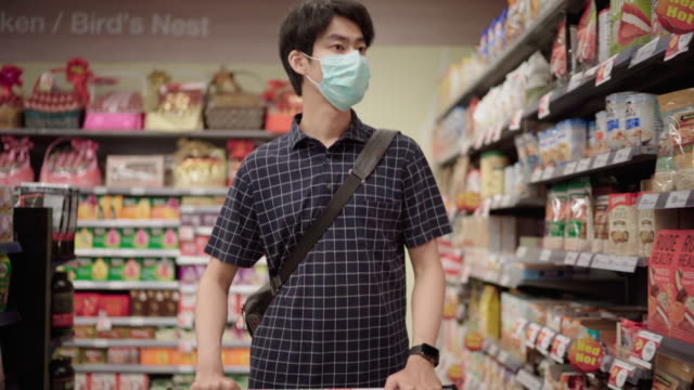 Young Man wearing a protective face mask shopping in supermarket