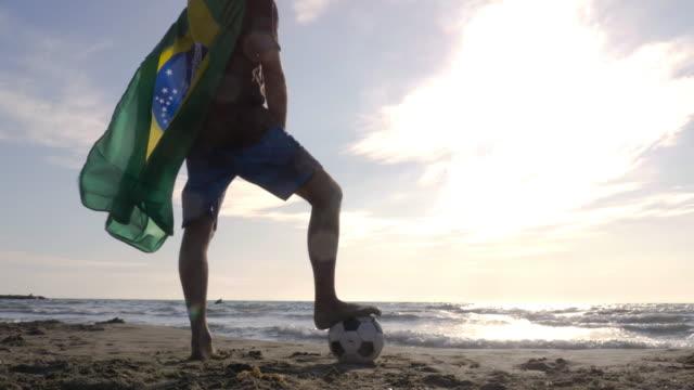 Jovem vestindo a bandeira nacional do Brasil Brasil como capa de super herói fica com pé na areia praia mar olhando para o mar na praia de cardan de sol câmera steadycam giram em torno de futebol - vídeo