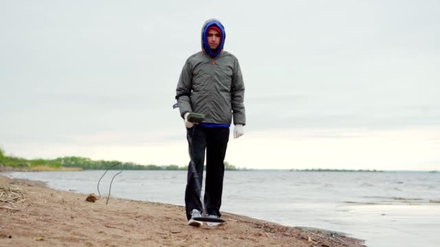 Young man wearing hood and using metal detector walking on beach along sea coastline on cold day