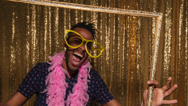 Young man wearing oversized glasses and holding a picture frame taking fun photos in the photo booth