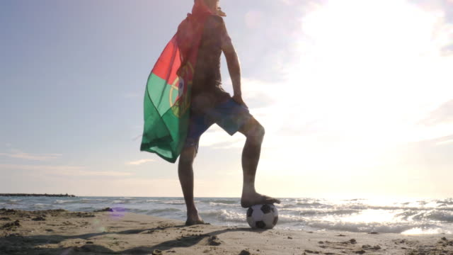 young man wearing portuguese portugal flag as cape stands with foot on football on the sea shore sand looking at the ocean at the beach at sunset camera steadycam gimbal revolving around - portogallo video stock e b–roll