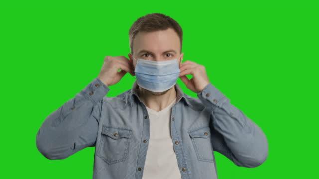 young man wearing protective mask at chroma key. bearded man in medical mask. - nakładać filmów i materiałów b-roll