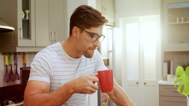 Jovem vestindo óculos sentado no banquinho, tomando um café enquanto usando laptop 4K 4K - vídeo