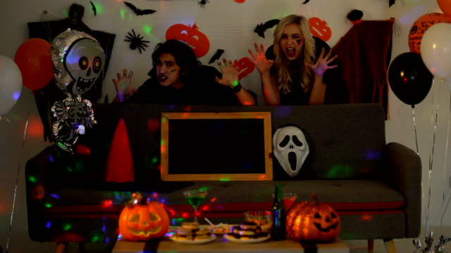 4K Young Man Wearing Vampire Costume With Beautiful Woman Wearing Witch Costume Hiding Behind Sofa And Having Fun At Halloween Party