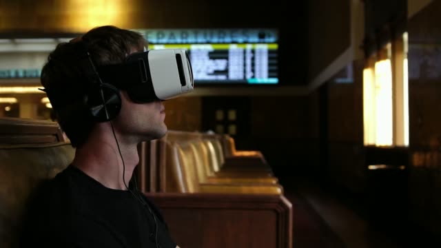 Young man wearing virtual reality headset watching 360 video in train union station video