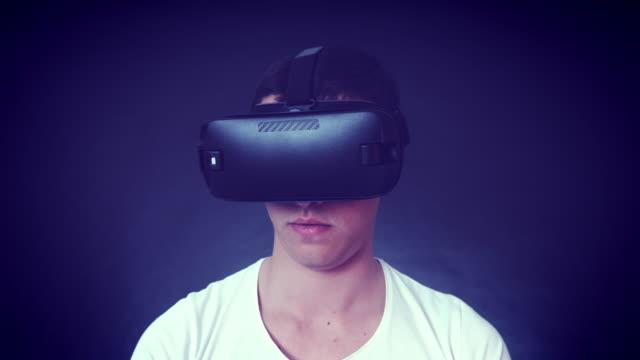 VR kulaklık giyen ve sanal gerçeklik karşılaşan genç adam video