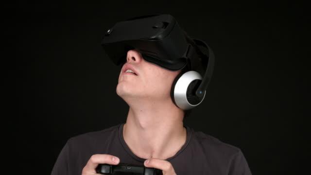 VR kulaklık giyen ve sanal gerçeklik oyunları oynamak genç adam video