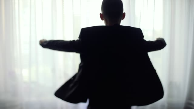 Young man wears a suit in front of the window video