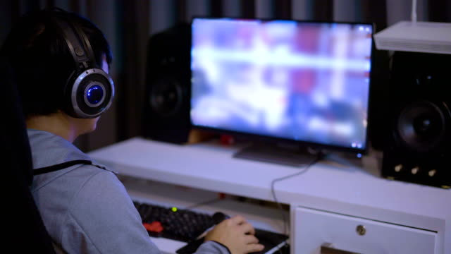 Young man wears and Gaming Headsets and playing video games at home.