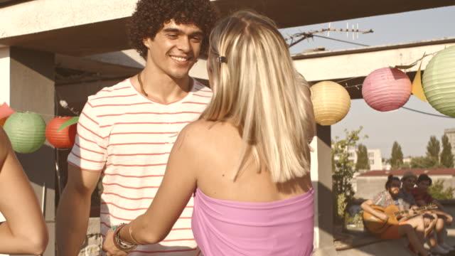 Hombre joven de bienvenida a los invitados para la fiesta en la azotea. - vídeo