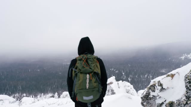 a young man with a backpack on his shoulders, stands on top of a snow-covered mountain and admires the landscape. - viaggiare zaino in spalla video stock e b–roll
