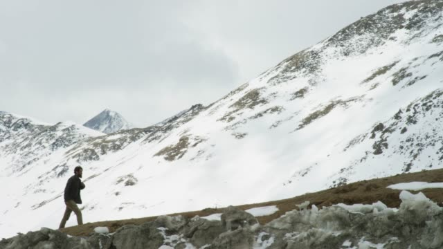 A Young Man with a Beard Hikes up a Snowy Mountain Near Loveland Pass (Continental Divide) in the Rocky Mountains of Colorado under an Overcast Sky