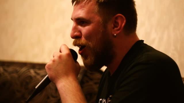 Young man with a beard singing karaoke video