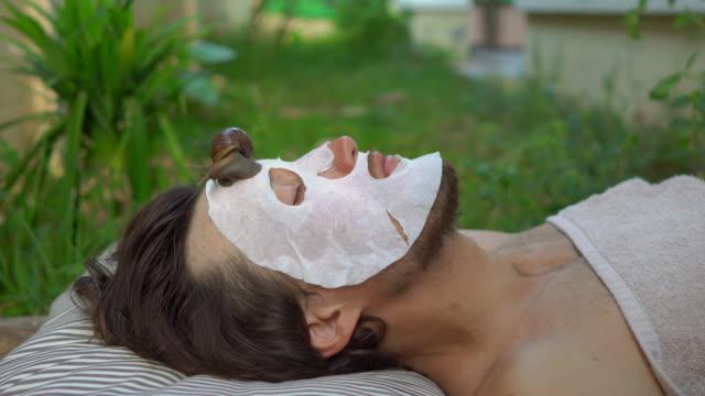 vidéos et rushes de jeune homme avec un masque de visage avec le mucus d'escargot. escargot rampant sur un masque de visage. spa pour homme, spa pour tous - pratique médicale