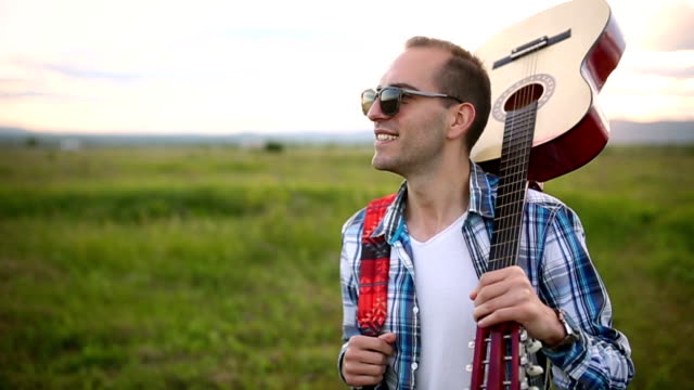 Young man with a guitar in the nature video