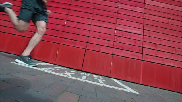A young man with a ripped physique running past a red wall in slow motion. video