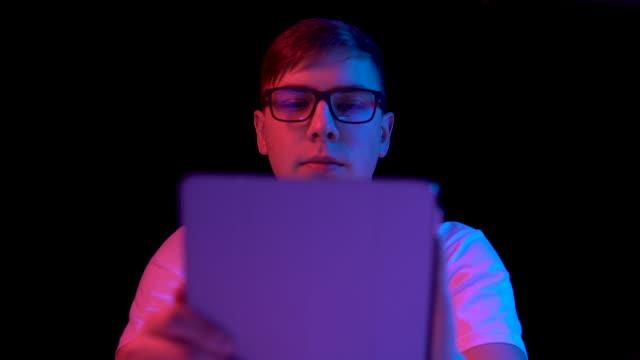junger mann mit tablette. ein mann benutzt eine tablette. blaues und rotes licht fällt auf einen mann auf schwarzem grund. - tablet mit displayinhalt stock-videos und b-roll-filmmaterial