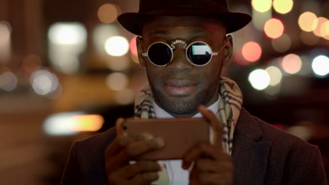 Young Man with African-American Ethnicity Wearing Old Classic Look. Having Fun in the Big City with Sunglasses, Hat and Scarf. video