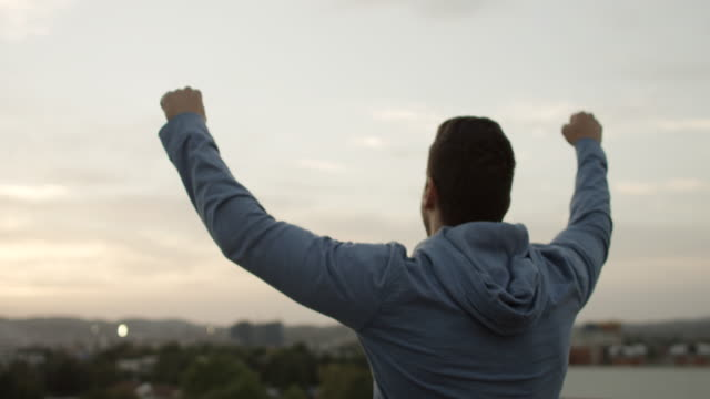 Young man with arms raised video