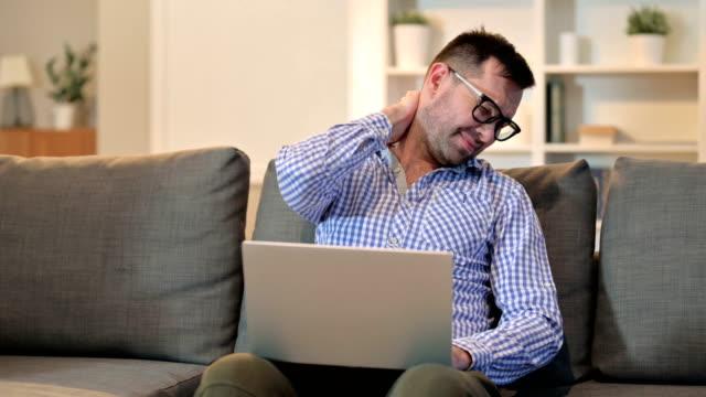 ung man med ryggont med laptop hemma - människorygg bildbanksvideor och videomaterial från bakom kulisserna