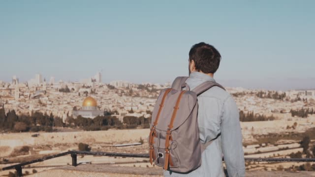 Young man with backpack at Jerusalem scenery. Thoughtful happy European male tourist walks away. Israel. Slow motion video