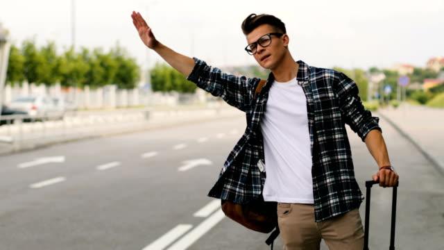 vidéos et rushes de jeune homme avec l'auto-stop de bagages sur la route en été ensoleillé jour quelques voitures dans l'aéroport. - homme faire coucou voiture