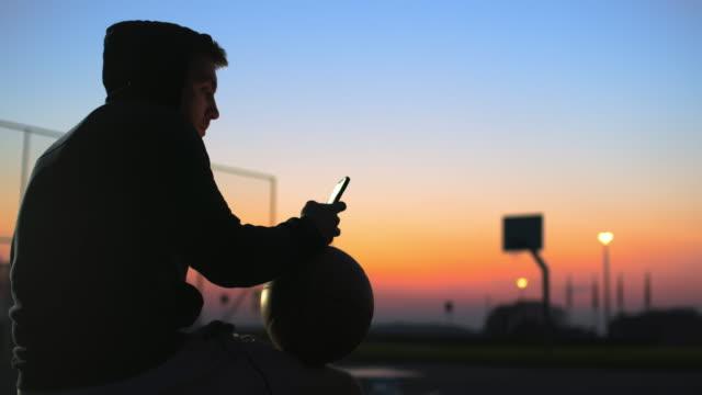 vidéos et rushes de jeune homme de ms avec le basket-ball et le téléphone intelligent sur le terrain extérieur de basket-ball au crépuscule - 20 24 ans