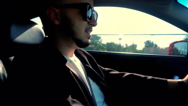 メガネのひげを持つ若者の乗り物車 ビデオ