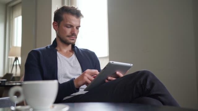 Young man with beard sitting at a caffe working on his digital tablet video