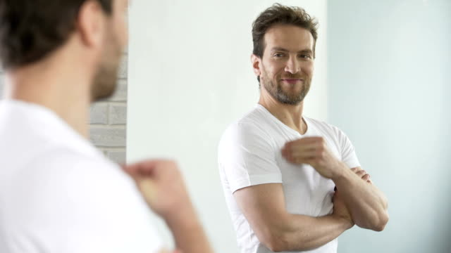 Young man with beautiful sports figure examining his reflection in mirror video