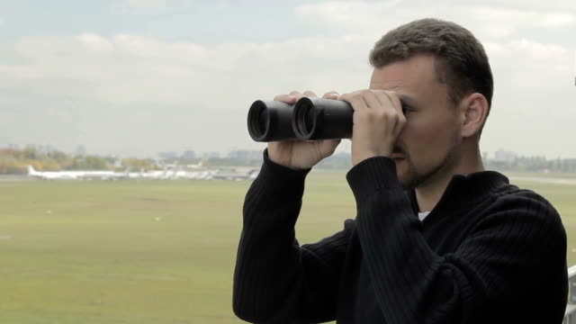 Young man with binoculars watches after planes in airport video