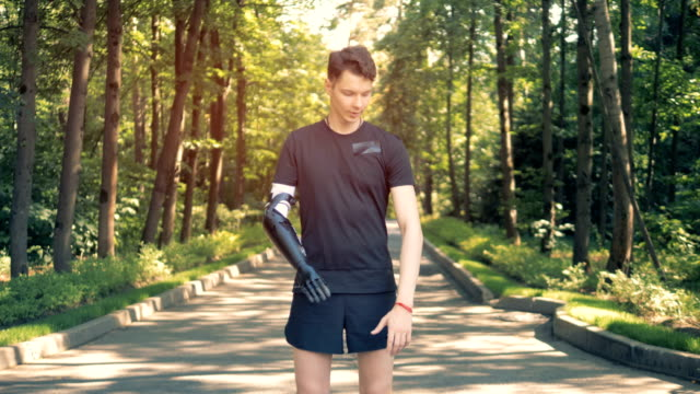 A young man with bionic arm in park. Futuristic human cyborg concept. A young man is standing in a green park and crossing his synthetic arm with a healthy one. 4K amputee stock videos & royalty-free footage