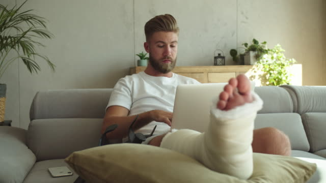 Young man with broken leg using laptop at home Young man with broken leg in plaster cast lying down on sofa at home and using computer. crutch stock videos & royalty-free footage