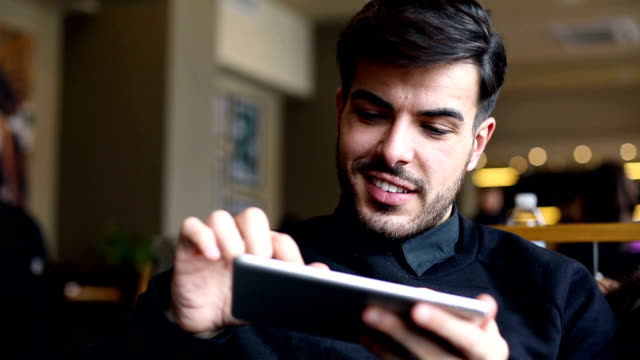 Young man with digital tablet in cafe video