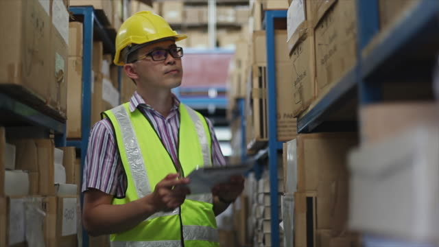 Young man with digital tablet in warehouse video