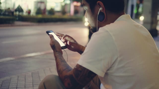 Young man with earphones in city.