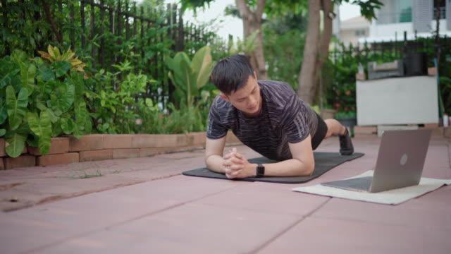 vídeos de stock e filmes b-roll de young man with fitness tracker stretching body at home - treino em casa