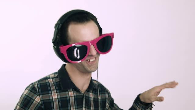 Hombre joven con gafas grandes y auriculares divertido - vídeo